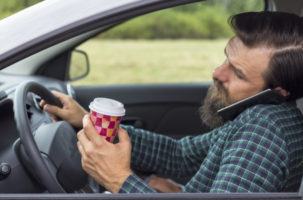 Distracted driver in a phon call holding coffee cup